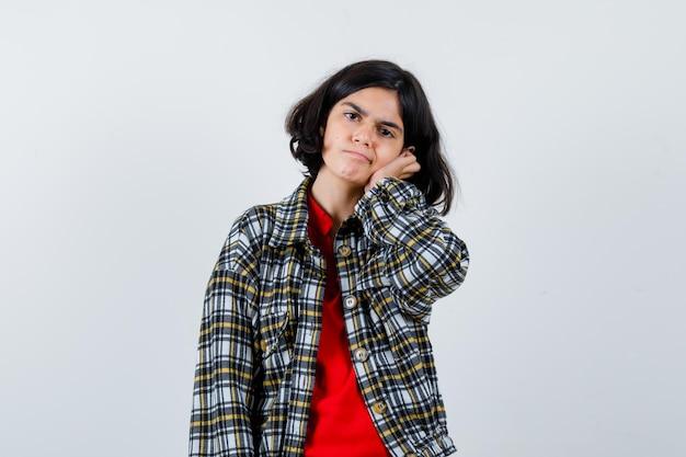 Chica joven en camisa a cuadros y camiseta roja, apoyándose en la mejilla de la palma y mirando seria, vista frontal.