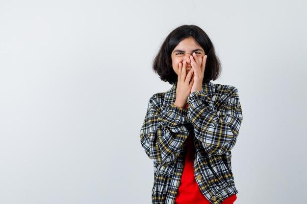 Chica joven en camisa a cuadros y camiseta roja cubriendo la boca con las manos, riendo y mirando feliz, vista frontal.