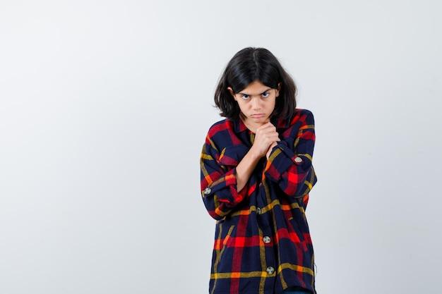 Chica joven en camisa a cuadros cogidos de la mano en el cuello y mirando exhausto, vista frontal.