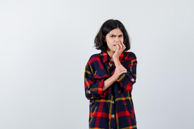 Chica joven en camisa de cuadros mordiendo los dedos mientras sostiene la mano en el brazo y mira emocionado, vista frontal.