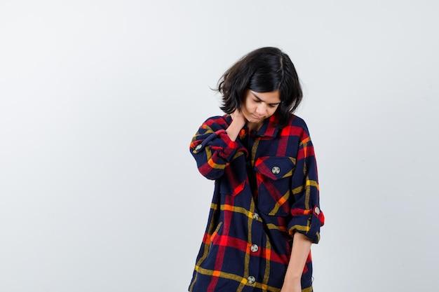 Chica joven en camisa a cuadros poniendo la mano detrás del cuello y mirando cansado, vista frontal.