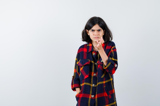 Chica joven en camisa a cuadros sosteniendo la mano en el bolsillo mientras apunta y mira furiosa, vista frontal.