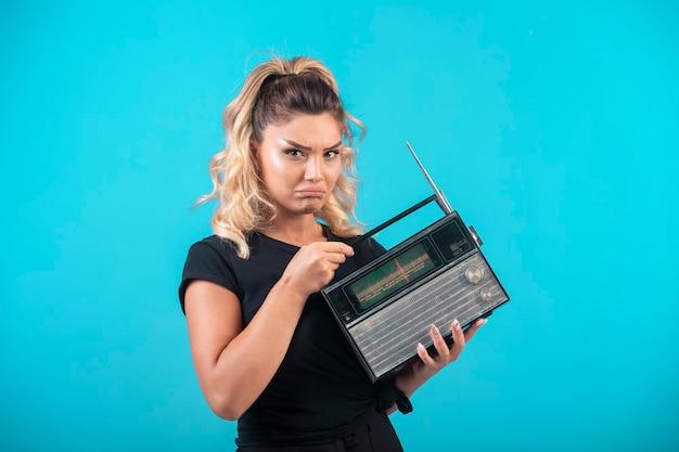 Chica joven en camisa negra sosteniendo una radio vintage y se siente decepcionada.
