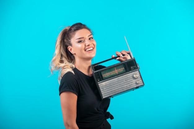 Chica joven con camisa negra sosteniendo una radio vintage y se siente positiva.