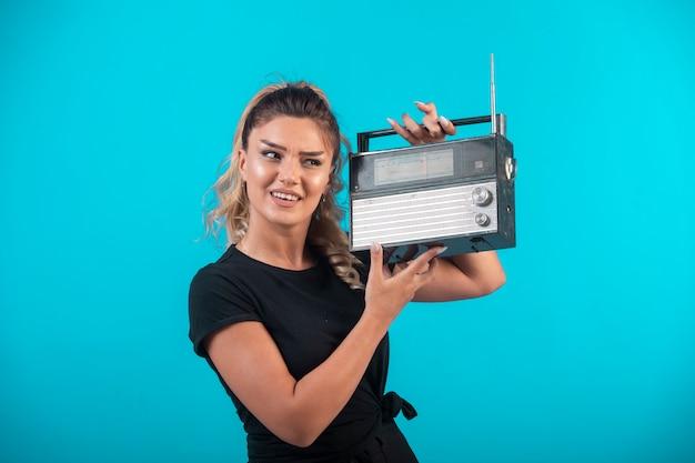 Chica joven con camisa negra sosteniendo una radio vintage en su hombro y se siente positiva.