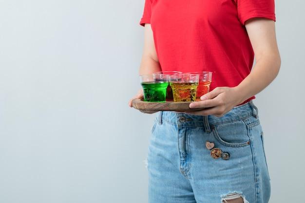 Chica joven en camisa roja sosteniendo una bandeja de madera de bebidas coloridas