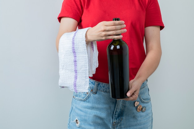 Chica joven en camisa roja sosteniendo una botella de vino