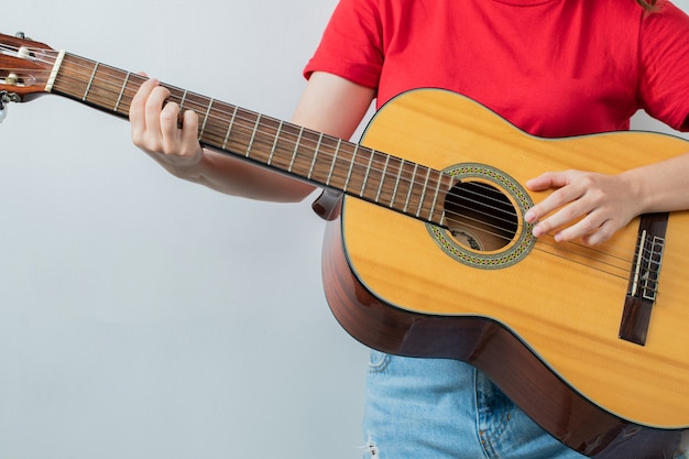 Chica joven en camisa roja sosteniendo una guitarra acústica