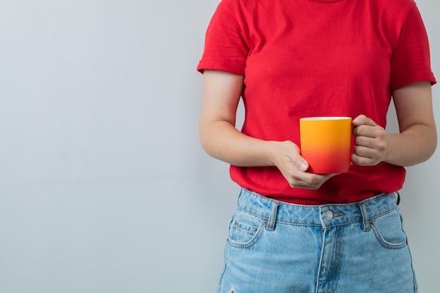 Chica joven en camisa roja sosteniendo una taza de bebida amarilla
