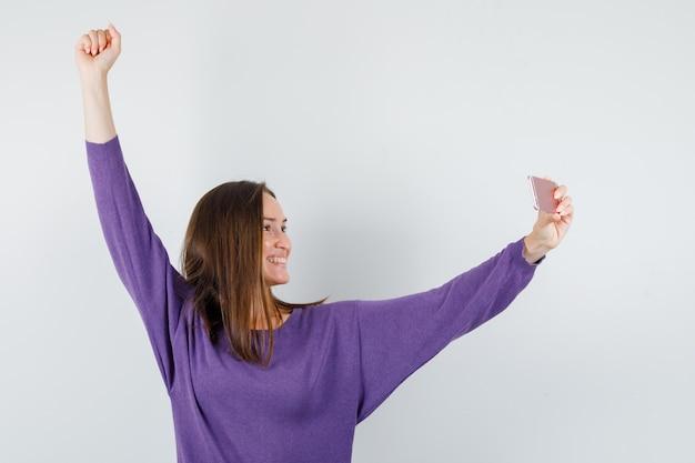 Chica joven en camisa violeta posando mientras toma selfie y parece feliz, vista frontal.