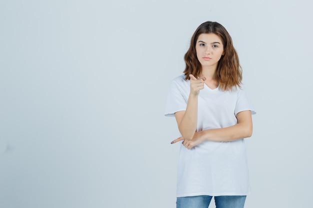 Chica joven en camiseta blanca apuntando a la cámara y mirando confiada, vista frontal.