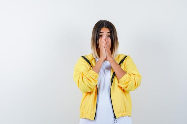 Chica joven en camiseta blanca, chaqueta amarilla juntando las manos delante de la boca y mirando emocionado, vista frontal.