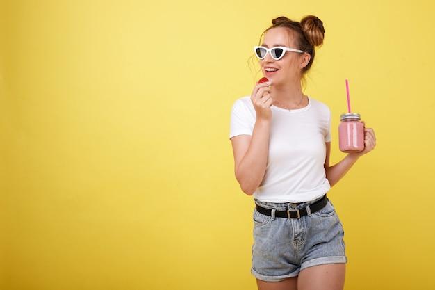 Chica joven en una camiseta blanca y gafas con fresas y batidos en un espacio amarillo. humor de verano