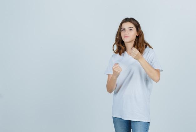 Chica joven en camiseta blanca, jeans de pie en pose de lucha y mirando confiado, vista frontal.