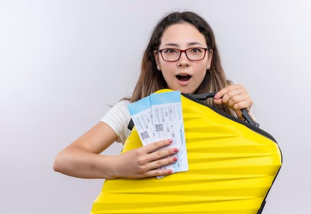 Chica joven en camiseta blanca con maleta de viaje y billetes de avión mirando salido y feliz