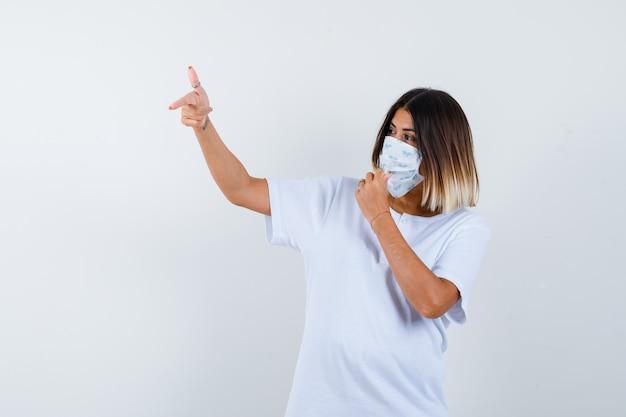 Chica joven con camiseta blanca y máscara apuntando hacia la izquierda con el dedo índice, sosteniendo la mano en la boca y mirando confiado, vista frontal.