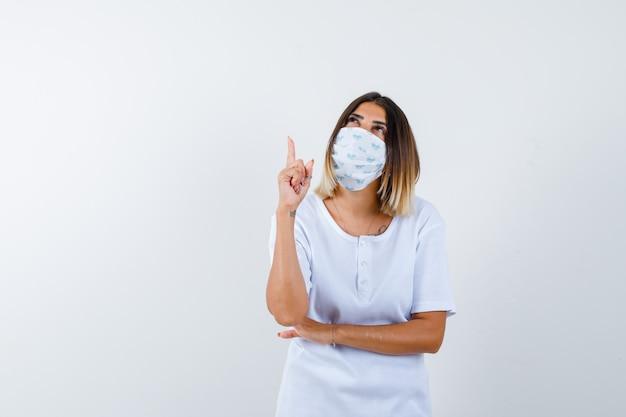 Chica joven en camiseta blanca, máscara levantando el dedo índice en gesto eureka mientras sostiene la mano debajo del codo y se ve sensible, vista frontal.