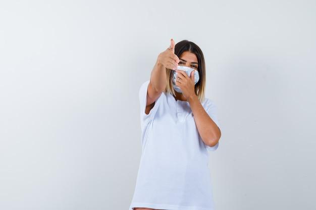 Chica joven en camiseta blanca, máscara mostrando gesto de pistola, cubriendo la boca con la mano y mirando confiado, vista frontal.
