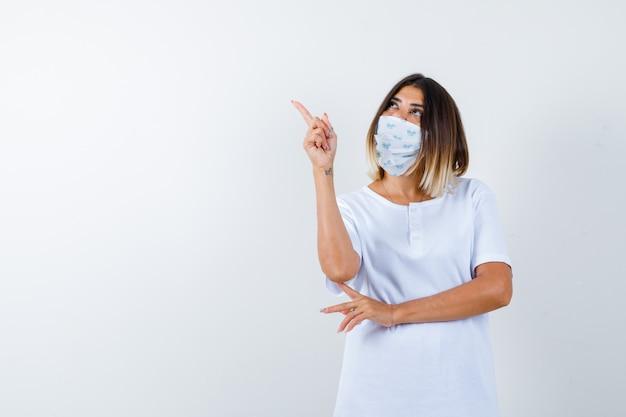 Chica joven en camiseta blanca y máscara sosteniendo una mano debajo del codo, apuntando hacia arriba con el dedo índice y mirando enfocado, vista frontal.