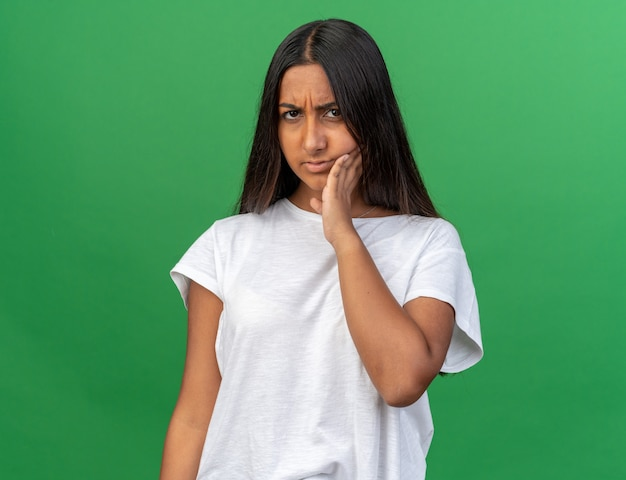 Chica joven en camiseta blanca mirando mal tocando su mejilla sintiendo dolor tener dolor de muelas de pie sobre fondo verde