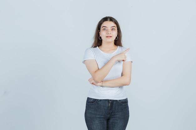 Chica joven en camiseta, jeans apuntando a un lado y mirando pensativo, vista frontal.
