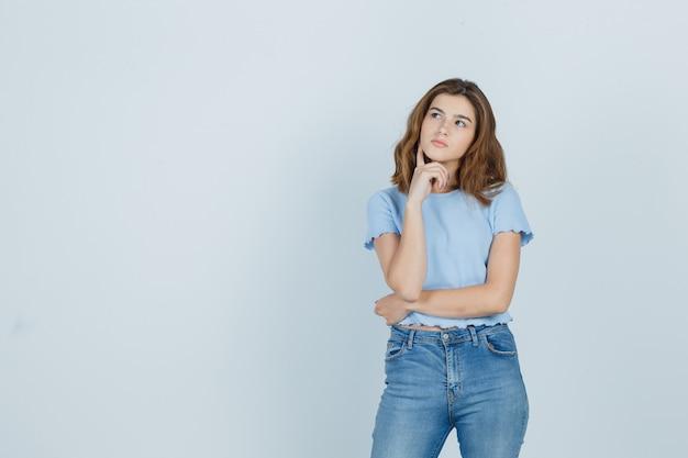Chica joven en camiseta, jeans sosteniendo el dedo en la barbilla y mirando pensativo, vista frontal.