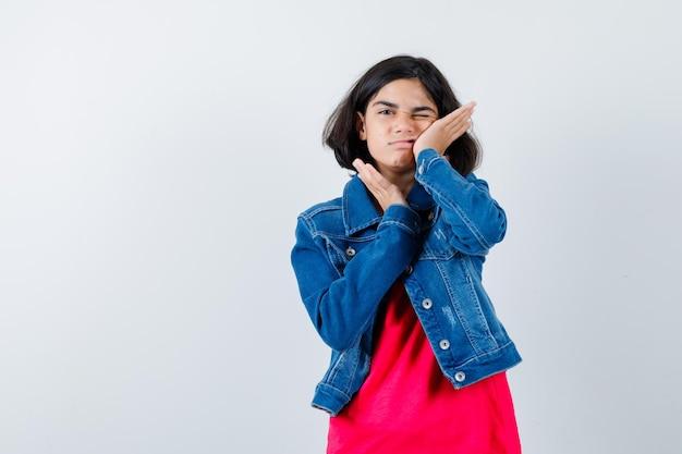 Chica joven en camiseta roja y chaqueta de mezclilla apoyada en la mejilla en la palma y mirando feliz, vista frontal.