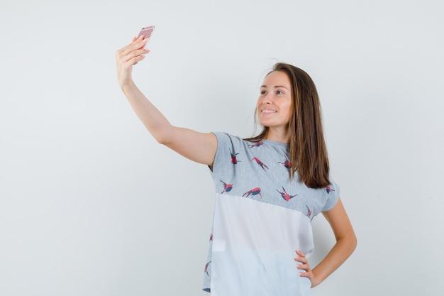 Chica joven en camiseta tomando selfie en teléfono móvil y mirando alegre, vista frontal.