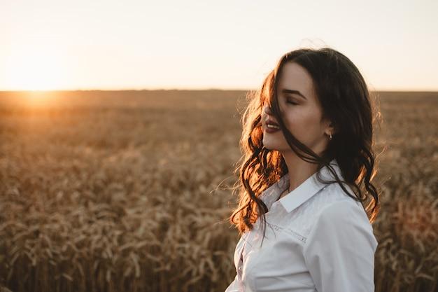 Chica joven en campo de trigo al atardecer.