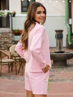 Chica joven con cara linda en pantalones cortos de color rosa mirando a la cámara y sonriendo afuera