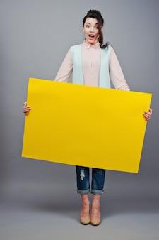 Chica joven con cara sorprendida mantenga papel en blanco amarillo. joven mujer sonriente mostrar tarjeta en blanco. muchacha con el retrato largo del pelo aislado en fondo gris.