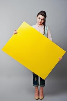 Chica joven con cara sostenga el papel en blanco amarillo. mujer joven muestra tarjeta en blanco. muchacha con el retrato largo del pelo aislado en fondo gris.