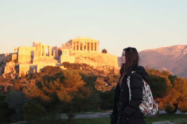 Chica joven cerca de acrópolis justo al atardecer, estudiante en atenas, grecia.