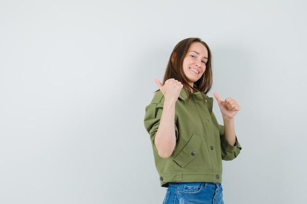 Chica joven con chaqueta, pantalones cortos apuntando hacia atrás con los pulgares hacia arriba y mirando alegre.