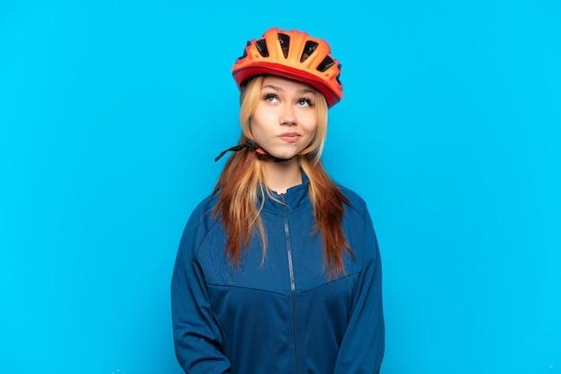 Chica joven ciclista aislada sobre fondo azul y mirando hacia arriba
