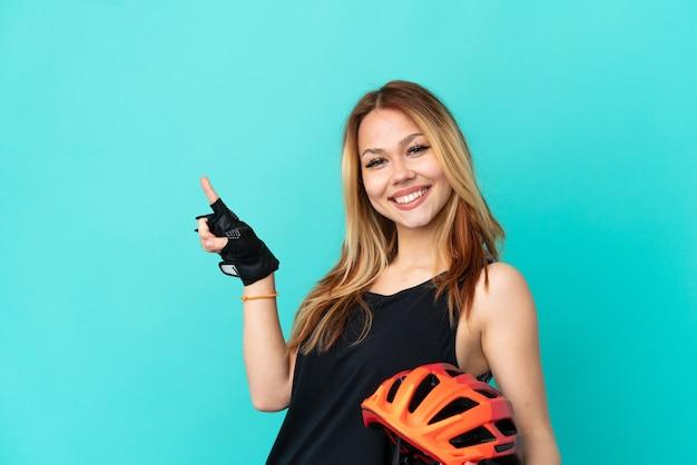 Chica joven ciclista sobre fondo azul aislado apuntando con el dedo hacia el lado y presentando un producto