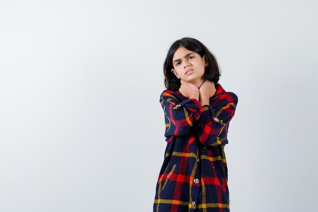 Chica joven cogidos de la mano en el cuello, tiene dolor de cuello en camisa a cuadros y parece molesto. vista frontal.