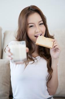 La chica joven está comiendo la tostada fresca que sostiene un vaso de leche