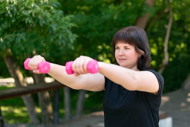 La chica joven está comprometida con pesas en el parque y mira hacia adelante. el entrenador muestra ejercicio para bíceps y tríceps