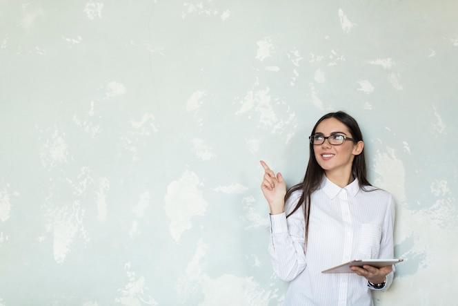 Chica joven con tableta apuntando hacia arriba