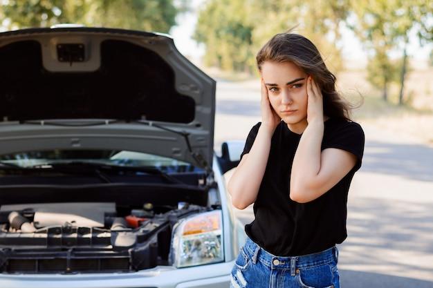 Chica joven conductora estresada con un coche averiado en medio de la nada esperando ayuda