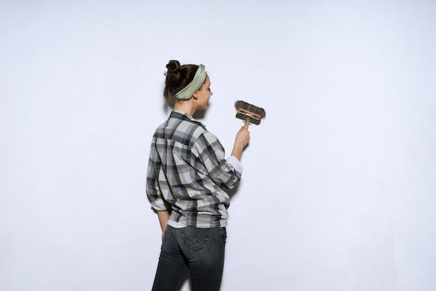Chica joven confiada en una camisa a cuadros colorea las paredes en blanco con un pincel, repara en un apartamento nuevo