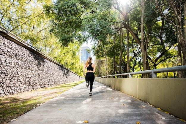 Chica joven corriendo al aire libre con ropa deportiva
