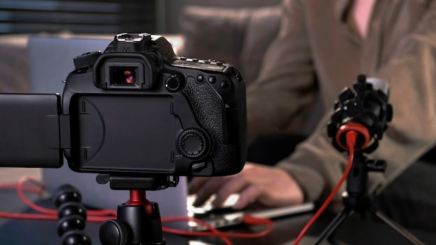 Chica joven creadora de contenido filmando a sí misma usando una cámara en un trípode y micrófono