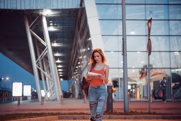 La chica joven cuesta por la noche cerca de la terminal del aeropuerto o estación y lee el mapa de la ciudad y busca el hotel.