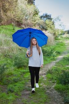 Chica joven dando un paseo con un paraguas azul