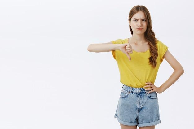 Chica joven decepcionada sonriendo y mostrando el pulgar hacia abajo disgustado, juzgando mal producto