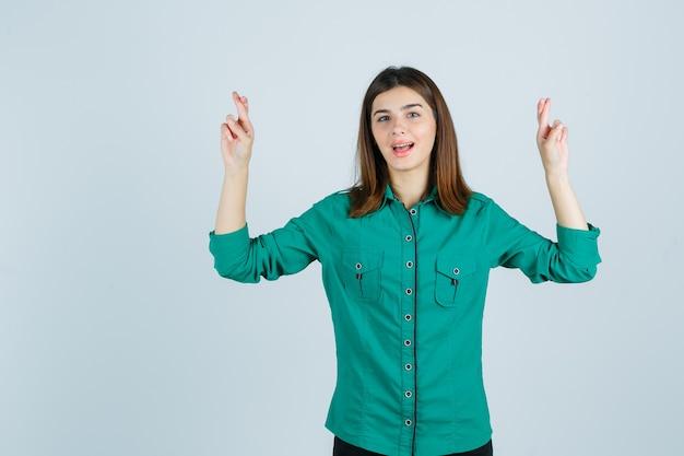Chica joven con los dedos cruzados, manteniendo la boca abierta en blusa verde, pantalón negro y luciendo feliz. vista frontal.
