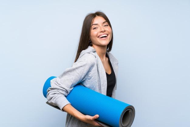 Chica joven deporte con estera sobre pared azul aislado