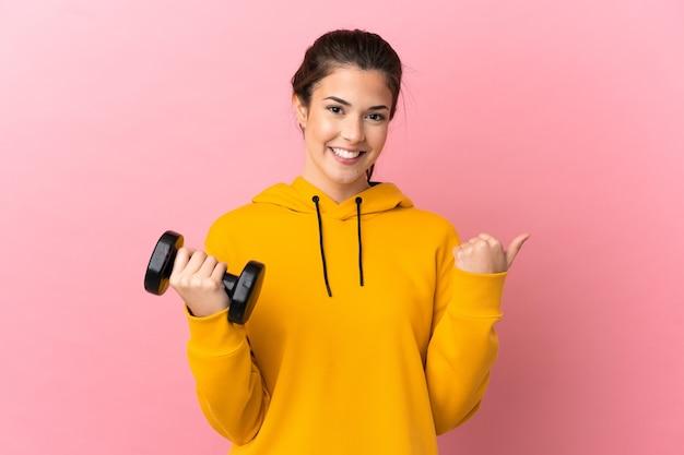 Chica joven deporte haciendo levantamiento de pesas sobre fondo rosa aislado apuntando hacia el lado para presentar un producto